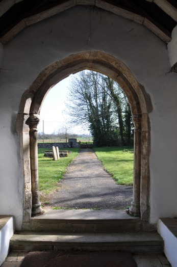 A view from inside looking out over the churchyard at Belchamp Otten