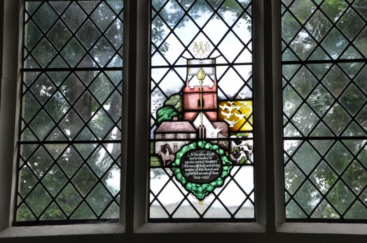 A memorial window dedicated to former church warden Dinah Warren, depicting the church tower, one of the oldest houses in the village and Dinah mounted on her horse.