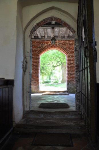 A view from within the church to the churchyard at Lamarsh